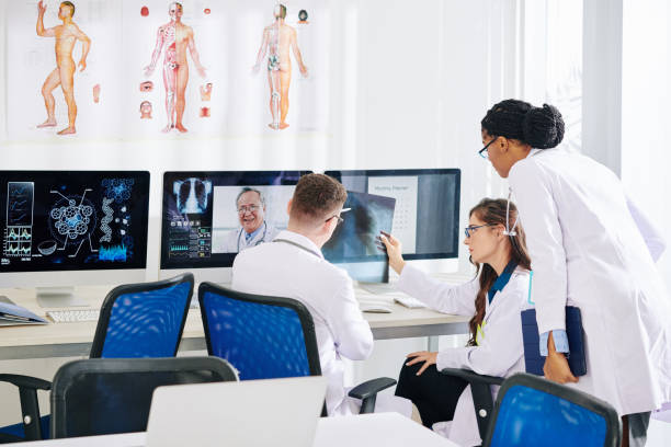Researchers talking to pulmonologist Group of medical researchers discussing lungs x-ray of patient with experienced pulmonologist medical technology stock pictures, royalty-free photos & images