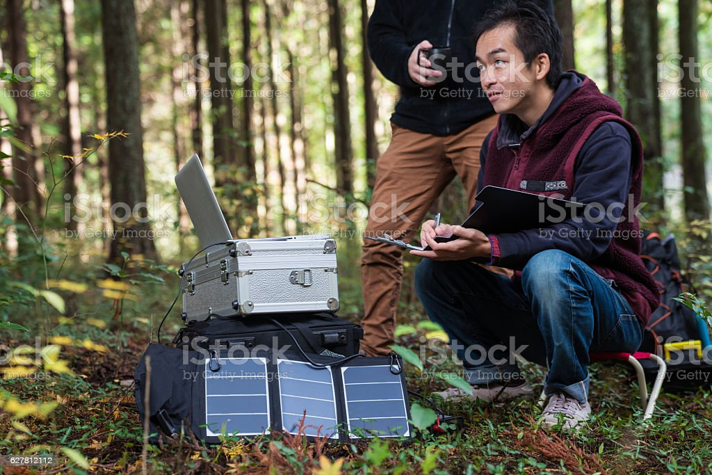Researchers working together at a remote solar powered field laboratory stock photo