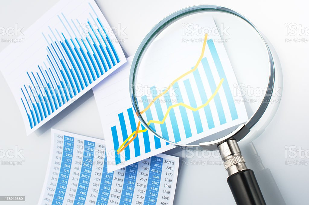 Researching and reading data with magnifying glass. stock photo