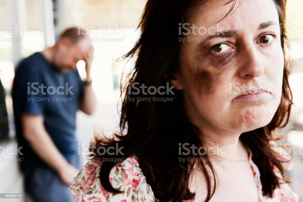 Resentful bruised woman with desperate looking man in  background stock photo