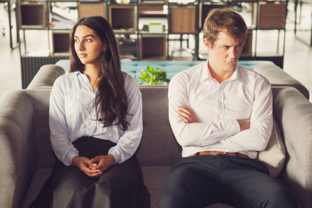 Resentful colleagues looking away from each other Resentful colleagues looking away from each other because of misunderstanding. Unhappy business people being quarreling and sitting on one sofa. Conflict concept asian couple arguing stock pictures, royalty-free photos & images