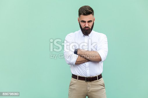 istock Resentful man, with arms folded, over light green background 836798060