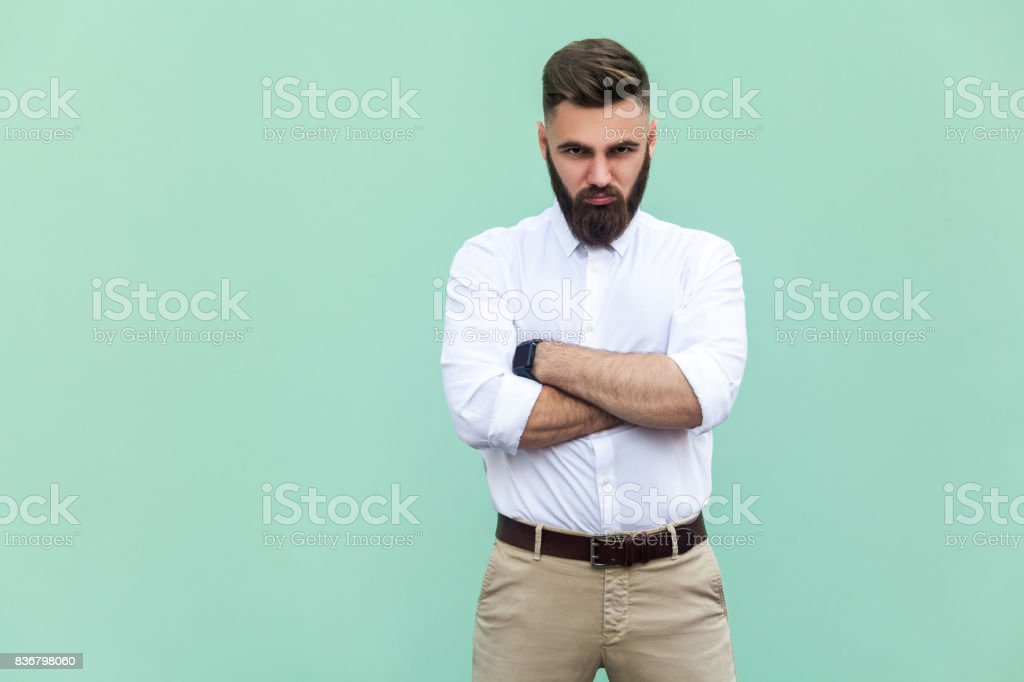 Resentful man, with arms folded, over light green background stock photo