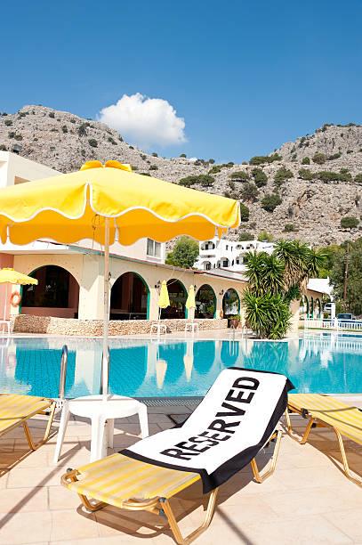 reserved'strandtuch mit einem leeren liegestuhl - sun chair stock-fotos und bilder