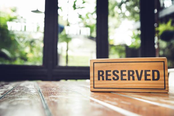 reservierte zeichen auf einem hölzernen tisch im restaurant. - geheime garten parties stock-fotos und bilder