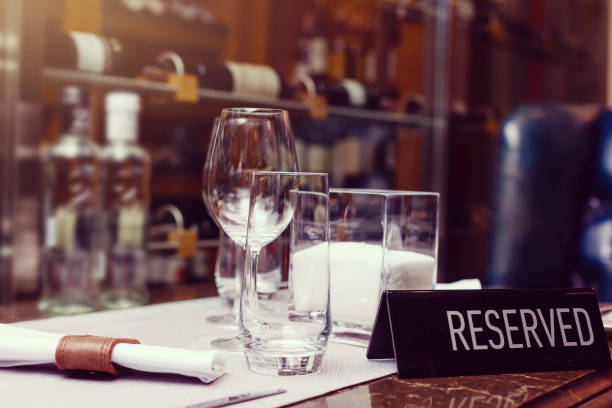 Reserved sign on a table in restaurant. Empty glasses set in restaurant Reserved sign on a table in restaurant. Empty glasses set in restaurant wildlife reserve stock pictures, royalty-free photos & images