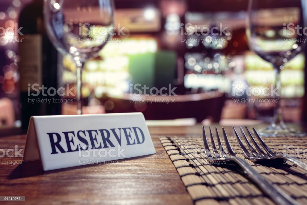 Reserved sign on restaurant table with bar background Restaurant reserved table sign with places setting and wine glasses ready for a party Advice Stock Photo