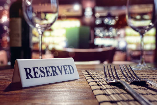 Reserved sign on restaurant table with bar background Restaurant reserved table sign with places setting and wine glasses ready for a party first class stock pictures, royalty-free photos & images