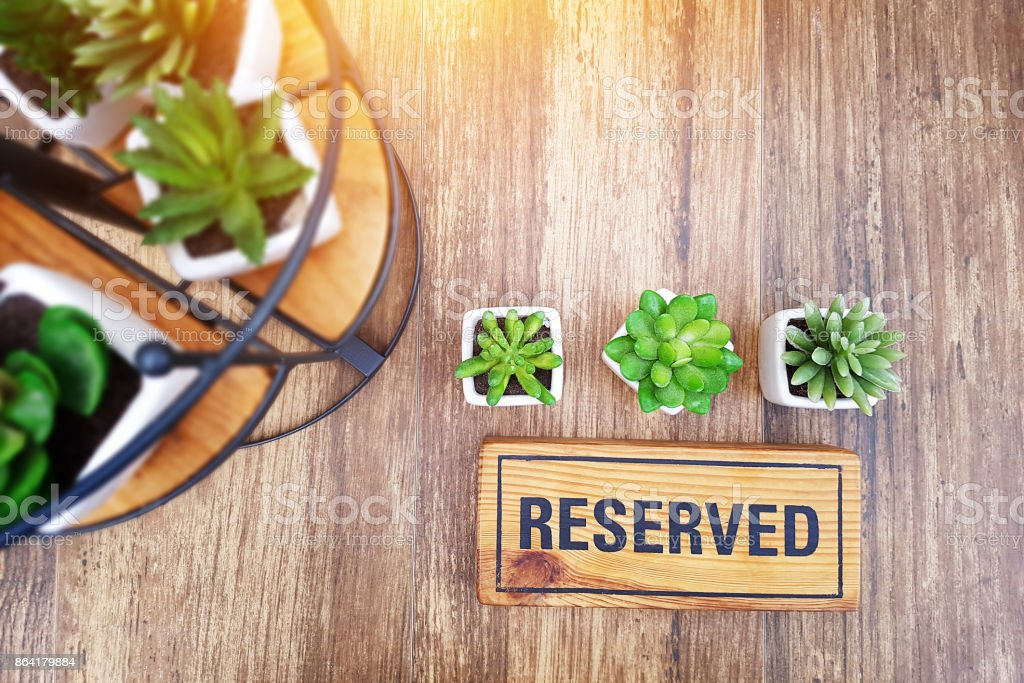 reserved sign on top of a wooden table in a restaurant, reservation seat at restaurant for dating on celebrate day concept, restaurant with reserved on table decorate with small cactus royalty-free stock photo