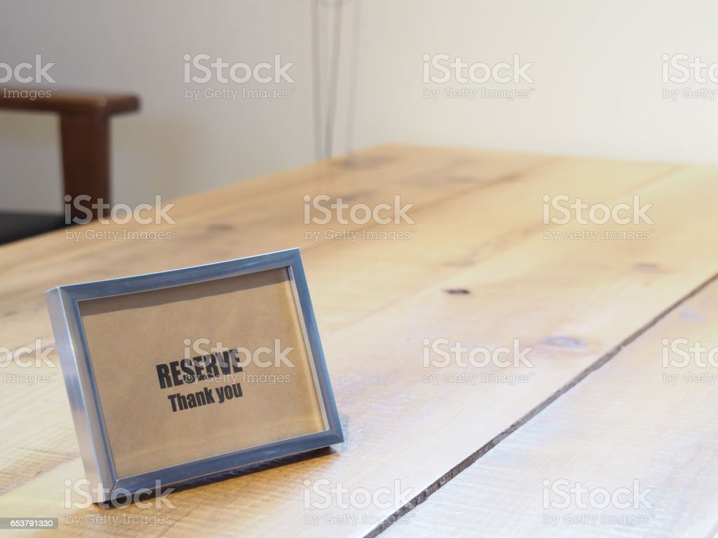 Reserved sign on wooden table in restaurant. stock photo