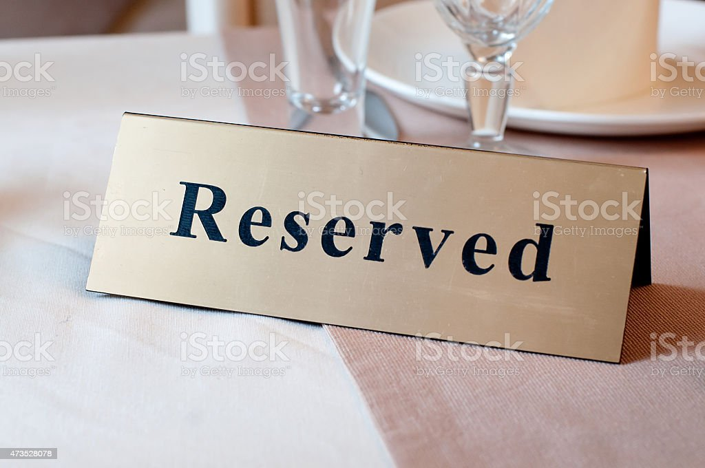 Reserved sign, reservation. On the table. Beige stock photo
