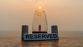 A reservered table sign with a unlite candle as the sun sets right into the glass