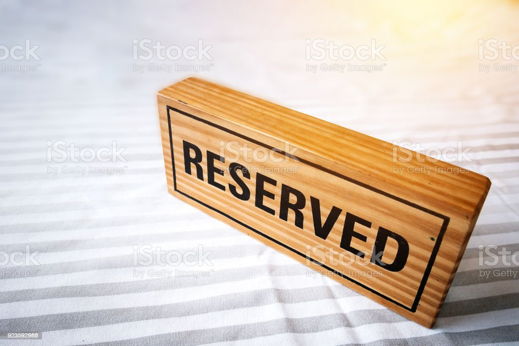reserved table. reserved wooden sign on table for reservation placed. reserved table in the restaurant. stock photo