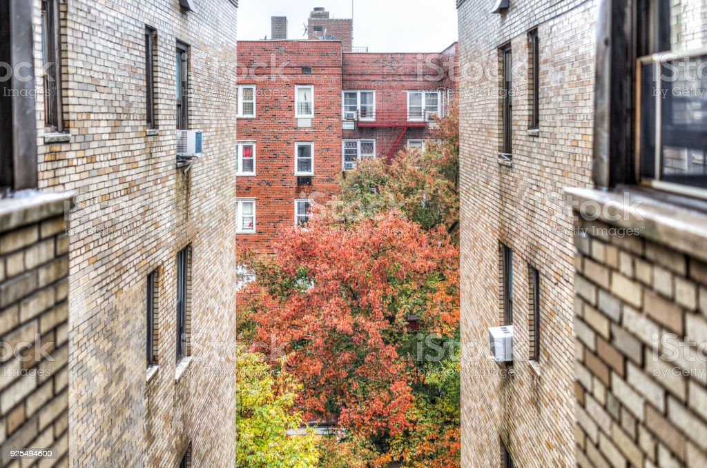 Residential apartment building and street road with sidewalk between in downtown Fordham Heights area in morning rain, fire escape stock photo
