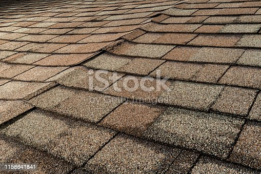 A view of a residential roof with architectural asphalt shingles that with various issues that can be signs of water damage and poor workmanship. The buckling of the shingles could be signs of the sheathing can be warping or delaminating from water penetration, which leads to a reroof.
