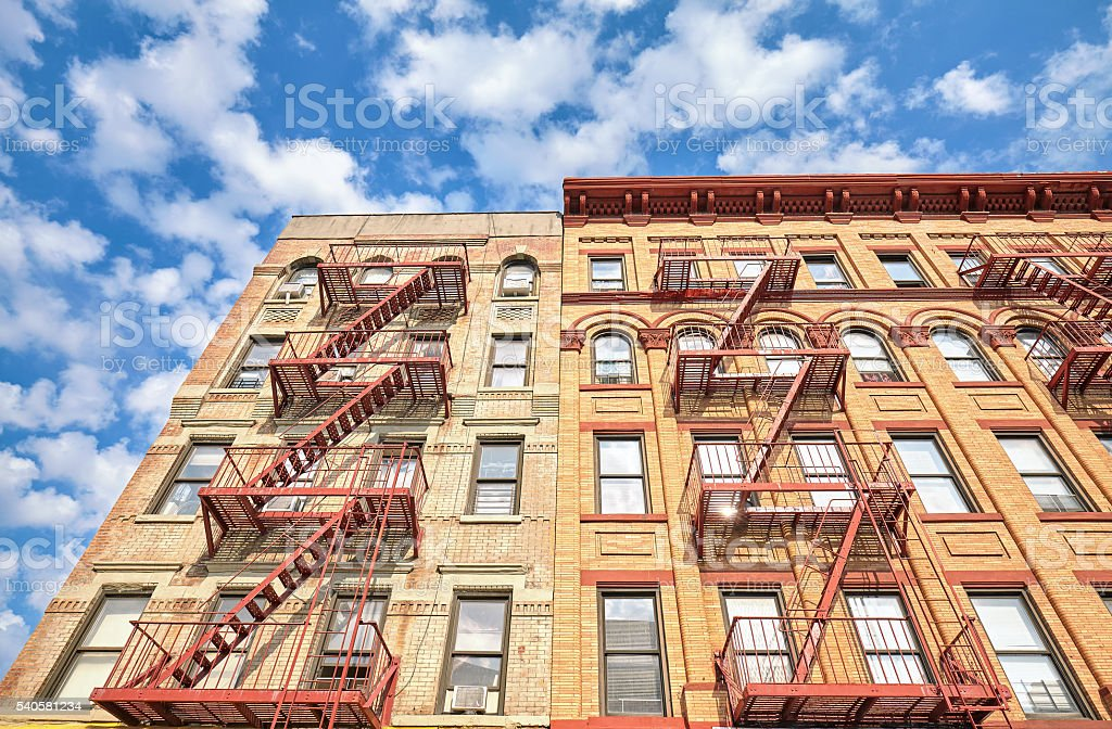 Residential building with fire escape ladders in NYC. stock photo