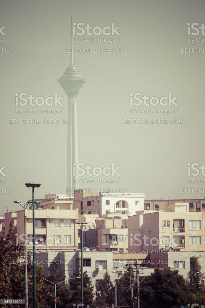 TEHERAN, IRAN - OCTOBER 03, 2016: Residential buildings in front of Milad Tower in air-polluted skyline of Tehran illuminated with golden sunset. stock photo