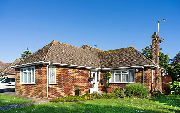 Residential bungalow home - UK A residential brick built bungalow home with a tiled roof built in 1955 and updated to include uPVC windows bungalow stock pictures, royalty-free photos & images