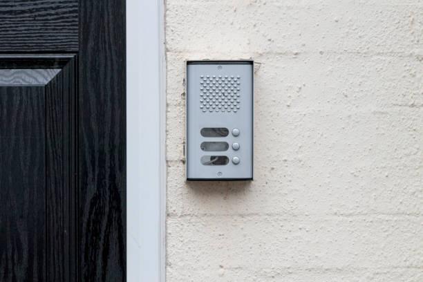residential buzzer intercom next to a black door on a white wall stock photo