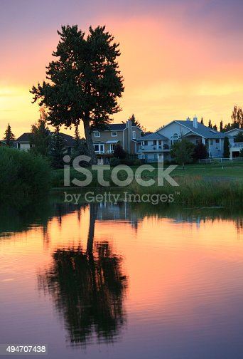A scenic pond reflection in a residential community. Nobody is in the image, taken on a warm summer evening with pristine pond reflecting an aspen trees. Houses are situated in an established neighbourhood in a small suburb of Calgary, Alberta, Canada. The suberb is also home to a golf course, which is also partially in the image. Beautiful, warm, sunset colours and rich tones highlight the scenic image of a small community in southern alberta.