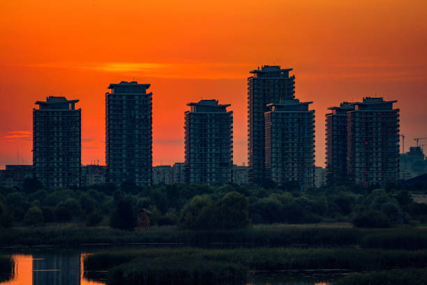 Residential complex located near a lake at sunset with the sun in the background stock photo