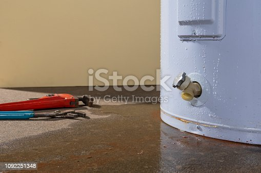 Water leaking from a residential electric water heater with a couple plumber's tools sitting on the concrete floor.
