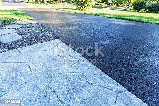 This suburban home asphalt driveway has just had a fresh blacktop resealing job finished. The black sealant is still wet; needing at least 24 hours to dry.