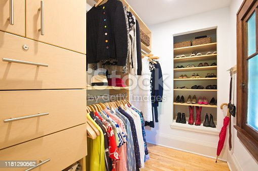 A walk-in closet in a U.S. residential home. featuring full height and half height clothes hanging storage, shoes shelves and drawers.