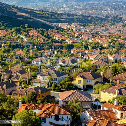 Residential homes on a sunny hill in San Clemente. Residential homes with landscaped lawn and trees in San Clemete, California, The homes are constructed on a sunny hill with gentle slopes.
