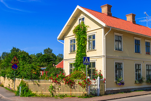 Residential house on a street corner with blooming roses