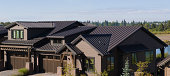 This image shows how attractive brown  metal roofing blends with modern residential architecture. Afternoon side lighting accentuates the pleasing lines of the roofing seams.