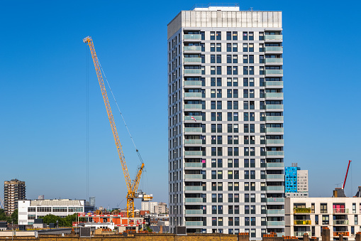 Residential new development high rise tower block with a crane in London against a cloudless sky