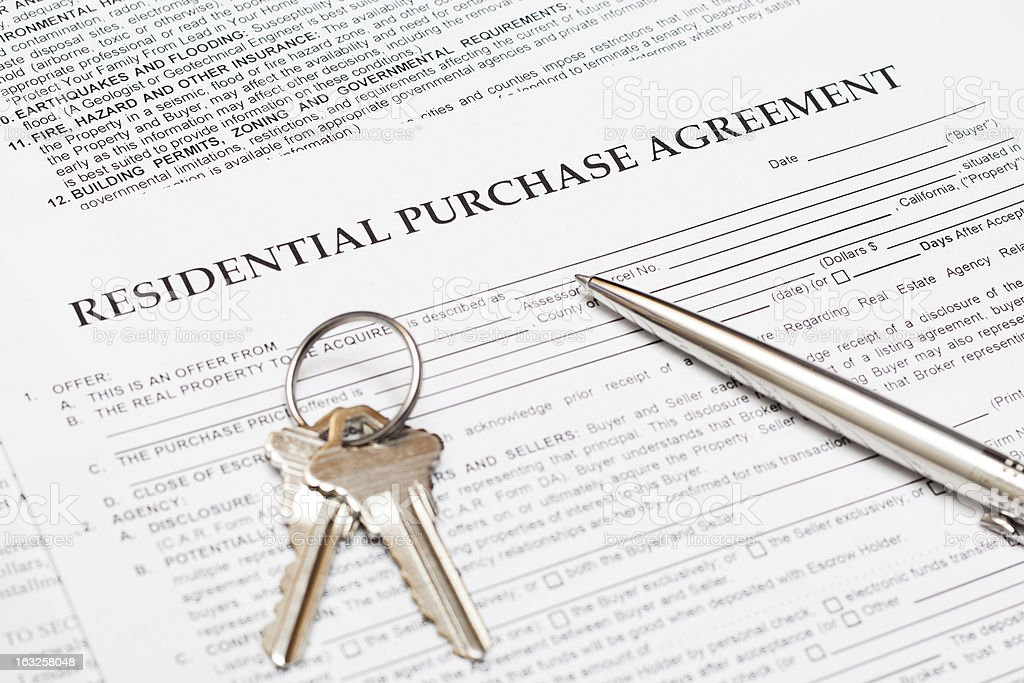 Real estate document with keys and pen.