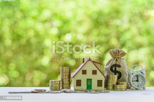 Residential real estate loan, financial concept : House model, coins, US dollar bag, white clock on a table, depicts home loan or borrowing money to buy / purchase a new home for first time homebuyer