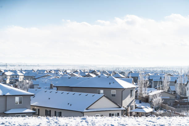 residential roofs in city in winter with snow covering them residential roofs in city in winter with snow covering them after snow fall urban sprawl stock pictures, royalty-free photos & images