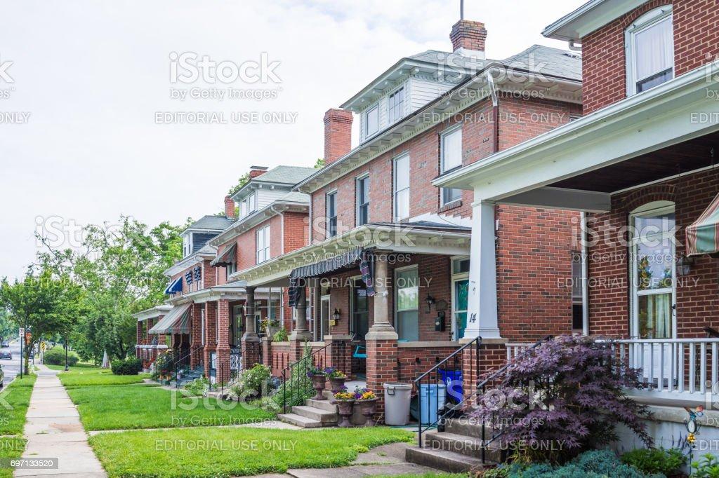 Linha residencial de casas no centro da cidade com arquitetura de tijolos e alpendres coloridos com flores no verão - foto de acervo