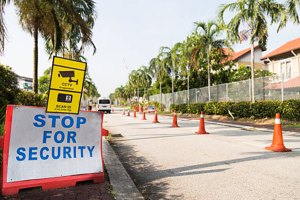 Residential security check point with boundary fencing Residential security check point at the entrance of a residential area. gated community stock pictures, royalty-free photos & images