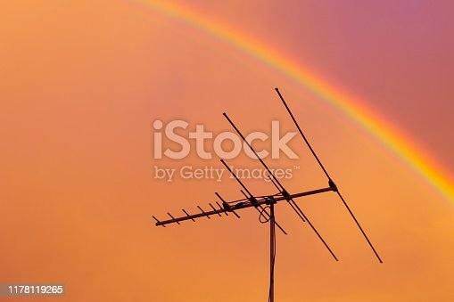 Residential tv antenna pointing directly through rainbow overhead.