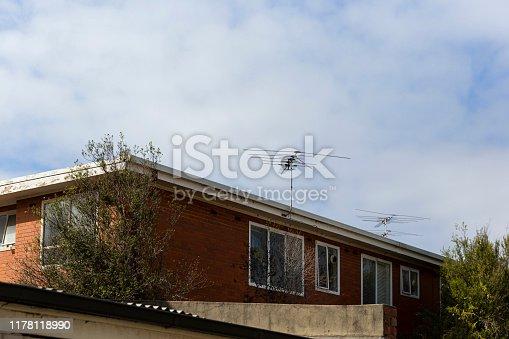 Residential tv antenna pointing toward beautiful blue winter skies.