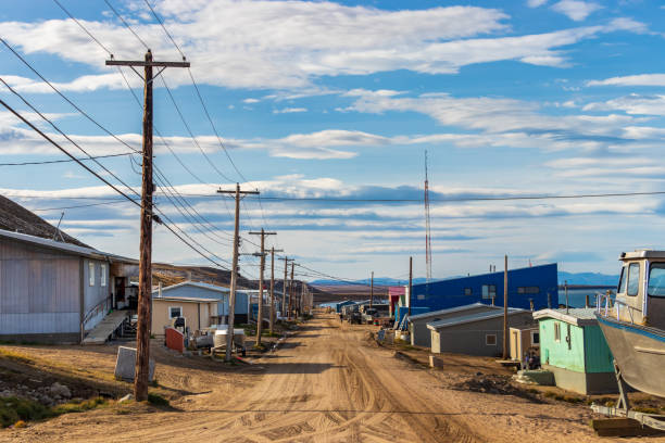 Residential wooden houses on a dirt road in Pond Inlet, Baffin Island, Canada. stock photo