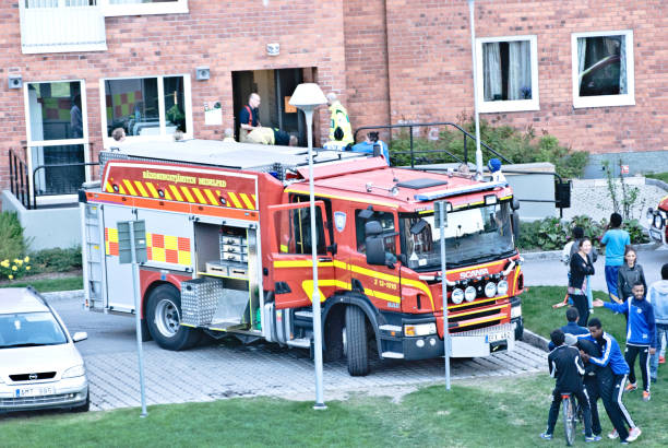 residents wait outside while swedish security & first responders work in a residential building in nacksta, sundsvall (north of stockholm) - sweden. - first responders zdjęcia i obrazy z banku zdjęć