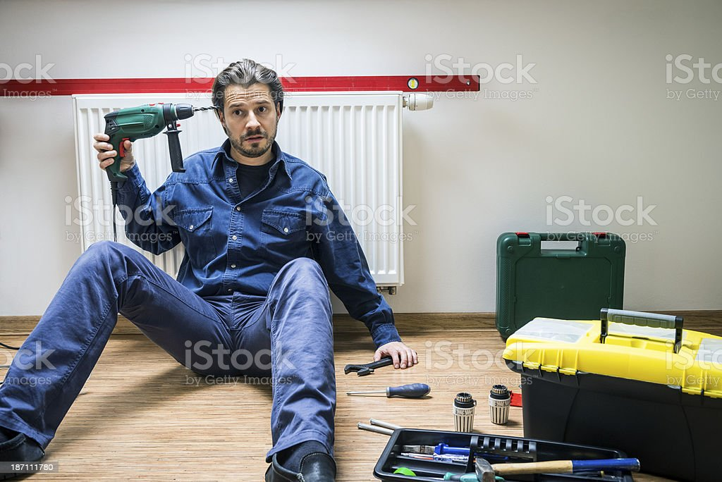 Resigned, tired, man is holding driller aimed to his head royalty-free stock photo