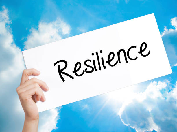 resilience sign on white paper. man hand holding paper with text. isolated on sky background - endurance stock pictures, royalty-free photos & images