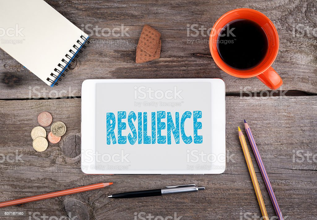 Resilience. Text on tablet device on a wooden table stok fotoğrafı