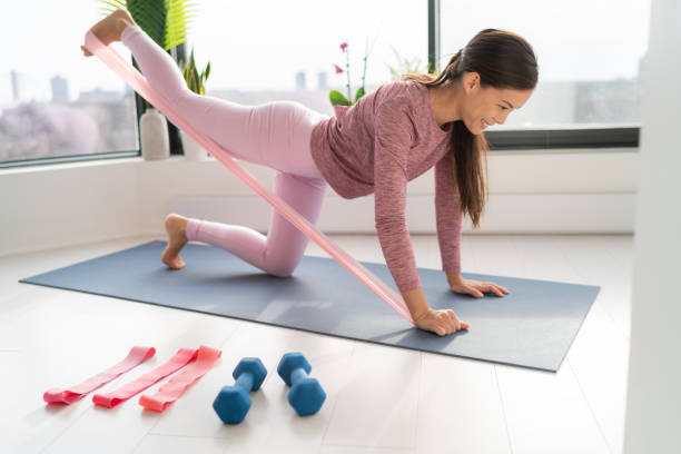 Resistance band fitness at home Asian woman doing leg workout donkey kick floor exercises with strap elastic. Glute muscle activation with kickback for thighs cellulite stock photo