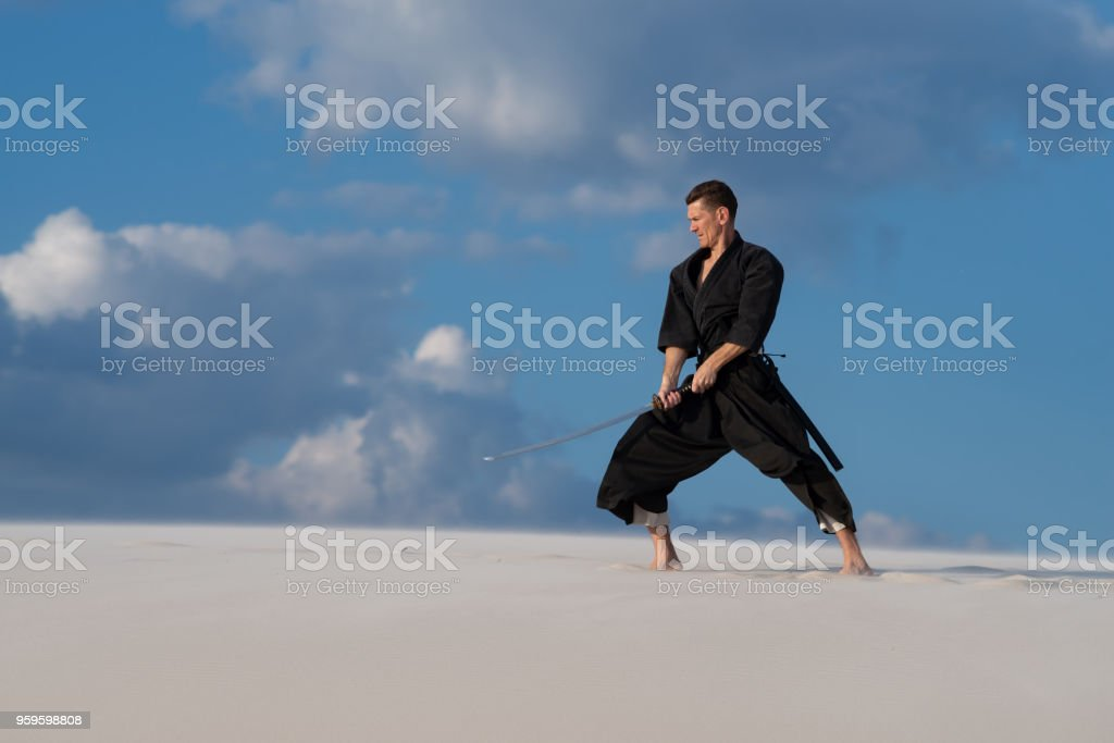 Resolute man practicing Japanese martial arts in desert стоковое фото