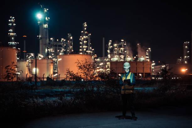 4K resolución Ingeniero petroquímico asiático el hombre trabaja tarde y duro con la tableta inteligente dentro de la fábrica de petróleo y gas industria de la refinería por la noche - foto de stock