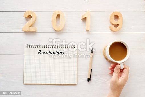 1057357020istockphoto 2019 resolution on blank notebook paper and hand holding coffee cup on white wood background, 2019 new year mock up, template, flat lay 1079566588