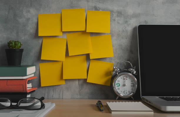 resolutions, notes, goals, post, memo or action plan concept. sticky notes on loft wall in workplace office with laptop, notebook, eye glasses, clock, plant, books and stationery on wooden desk. - bulletin board stock pictures, royalty-free photos & images