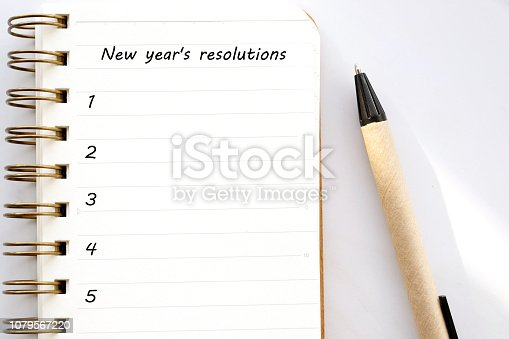 1057357020istockphoto 2019 resolutions on blank notebook paper on white marble background, 2019 new year mock up, template, flat lay 1079567220